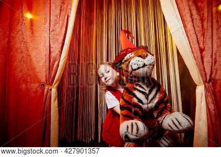 Small Girl During A Stylized Theatrical Circus Photo Shoot In A Beautiful Red Location With Tiger. Y