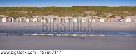 Beach Huts On Dutch Wadden Island Of Texel At Dusk Under Blue Sky In Summer In The Netherlands