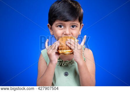 Girl Kid Enjoying Eating Of Tasty Burger On Blue Background - Concept Of Children Unhealthy Eating H