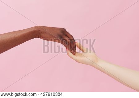 Hands Of A Caucasian Woman And An African American Man Touching Each Other Lightly Against A Pink Ba