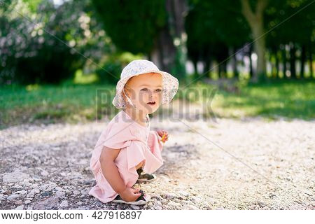 Little Girl In A Hat Squatted On A Gravel Path In The Park
