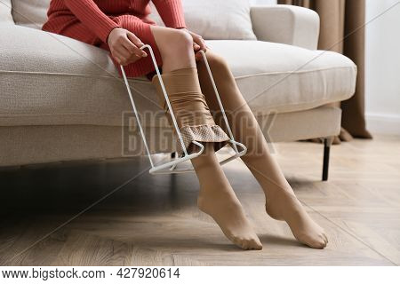 Woman Wearing Compression Tights With Donner In Living Room, Closeup