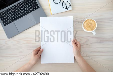 To Do List Or Organizing Plans. Woman Holding Sheet Of Paper, Sitting At Desk With Laptop And Cup Of