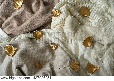 Pile Of Knitted Clothes With Autumn Gold Leaves, Warm Background, Knitwear, Space For Text, Autumn W