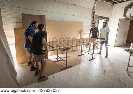 Team Of Carpenters Making Furniture In A Workshop. Woodworking And Crafts Tools