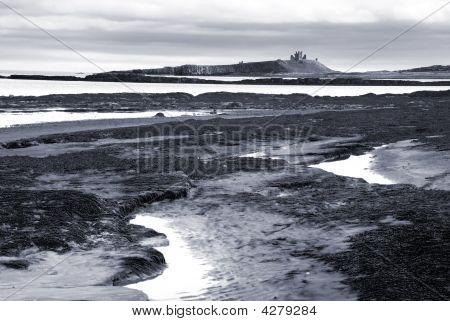 Dunstanburgh Castle From Embleston Beach At Low Tide (black And White)