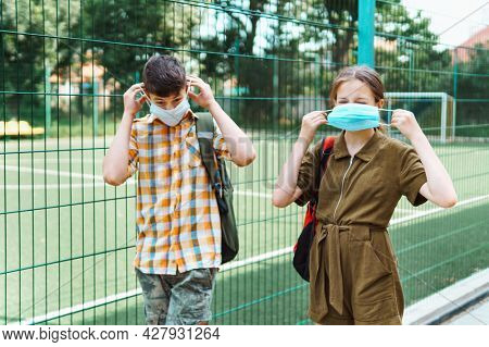 two teenagers boy and girl on the way to the school, they use protective face masks to protect against virus, coronavirus infection, education and back to school concept