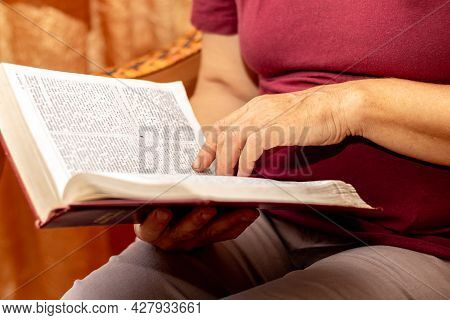 An Elderly Woman Is Reading The Bible. Bible In The Hands Of An Elderly Woman