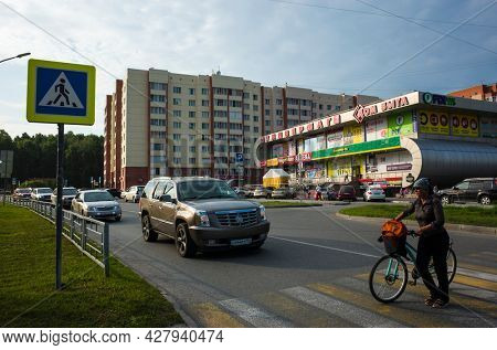 Koltsovo, Novosibirsk, Russia - 24 July, 2021: Car Cadillac stops in front of pedestrian crossing for woman with bicycle crosses road near department store, Work settlement of Koltsovo, Roads Siberia