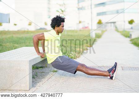 Black Man Doing Triceps Dip Exercise On City Street Bench.