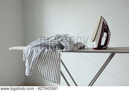 Iron And Ironing Board In A Bright Room. Iron Clothes.