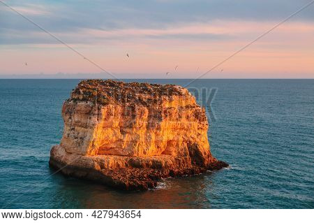 Rock at sunset light on famous beach of Praia dos Caneiros. Algarve.Portugal