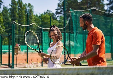 Instructor Showing A Proper Tennis Grip Technique To His Client