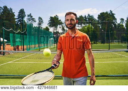 Male Beginner Tennis Player Mastering The Serve Technique
