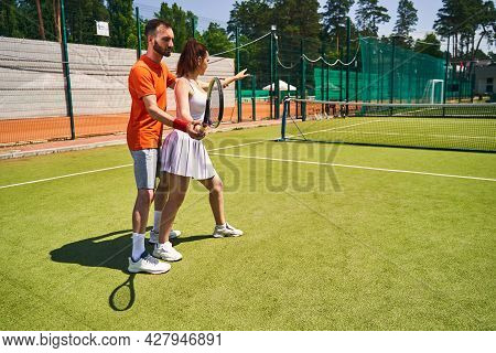 Experienced Trainer Teaching A Beginner Player To Hold The Racket