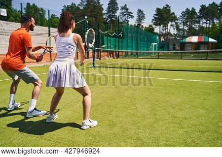 Instructor And His Client Practicing A Proper Tennis Stance