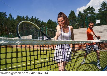Joyous Tennis Player And Her Partner Perfecting Their Serve Technique