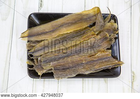 Eel (latin Anguilla) Dried Cut Into Strips On A Black Rectangular Plate With A Wooden Table Backgrou