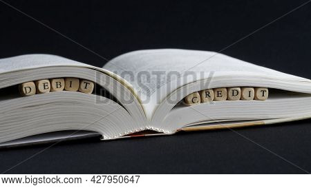 Inscription Debit Credit Next To An Open Book On A Dark Surface. The Concept Of Accounting And Bookk