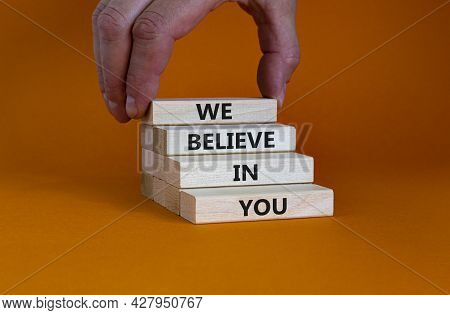 We Believe In You Symbol. Concept Words 'we Believe In You' On Wooden Blocks On A Beautiful Orange B