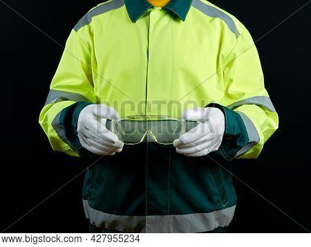 A Worker Holds Safety Glasses In His Hands. Safety At Work, Vision Protection At The Factory. A Man
