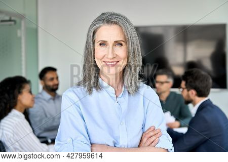 Happy Older Senior Woman Business Leader Standing In Office Working With Team People. Smiling Middle