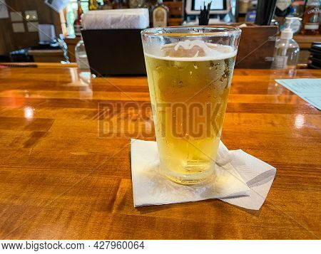 A Cold Draft Beer In A Glass Sitting On A Bar In Florida.