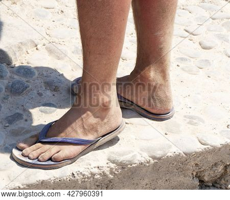 Male Legs In Slippers. A Mature Man In Slippers With Bare Feet