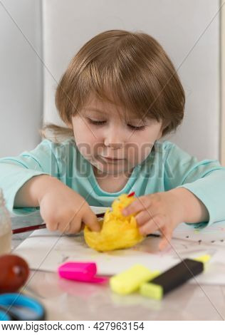 A Three-year-old Girl In A Turquoise Blouse Is Enthusiastically Making A Yellow Chicken At The Table