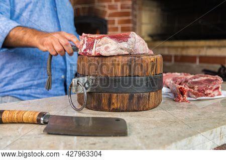 A Man Cuts Raw Meat On A Deck. Fresh Meat On A Cutting Board.