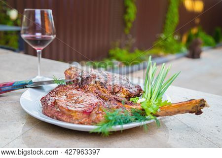 Cooked Fried Meat With Spices On A White Plate. Oven-baked Meat For Dinner With A Glass Of Red Wine.