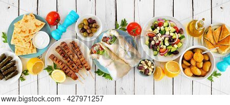Greek Food Table Scene, Top View On A White Wood Banner Background. Variety Of Items Including Gyros