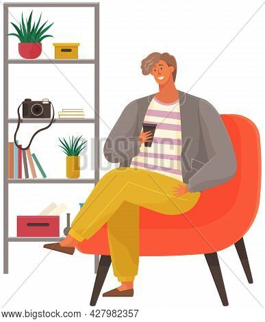 Stylish Man Sitting On Armchair Holding Cup In Hand Drinking Coffee. Male Character Has Rest In Apar