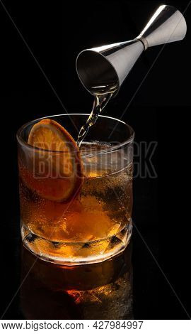 Alcoholic cocktail Old fashioned cocktail with orange slice, spilling bourbon from the double jigger on black background. Copyspace