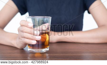 Woman With Black T-shirt Holding Whiskey Or Alcohol In Glass On Wooden Table. Substance Abuse, Addic