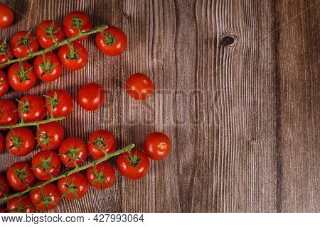 Trusses Of Small Cherry Tomatoes On Wooden Background With Copy Space