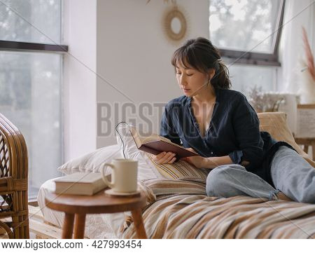 Young Relaxed Asian Woman In Casual Outfit Reading Book And Drinking Tea While Relaxing On Sofa At H