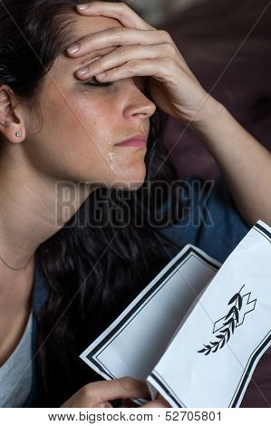 Portrait of crying young woman holding obituary