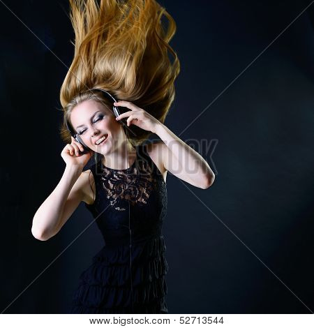 Music girl. Young beautiful excited woman with headphones listening music and dancing with long blond hair fly-away against dark background