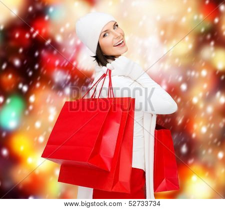 retail and sale concept - happy woman in winter clothes with shopping bags