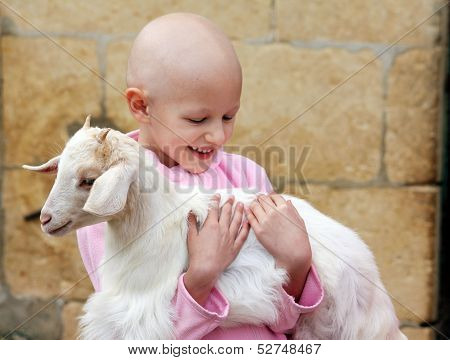 a caucasian child suffering from cancer holding a goat poster