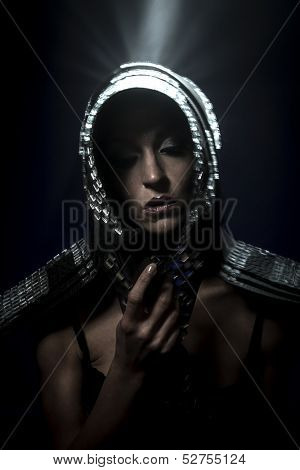 Beautiful brunette woman in armor formed by mirrors