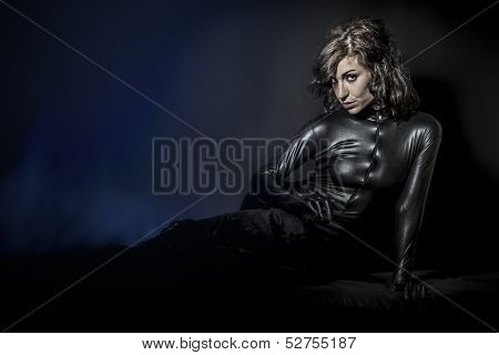 Beautiful brunette woman wearing latex dress on dark background, lying