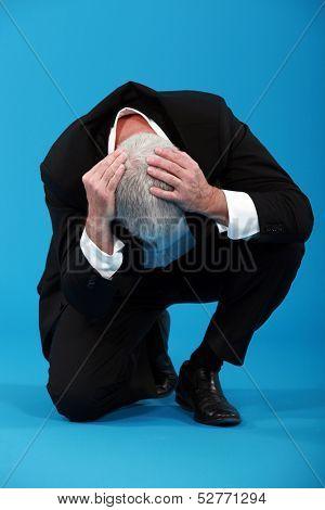 Businessman holding his head in despair