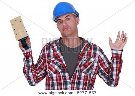 Construction worker holding up a sander