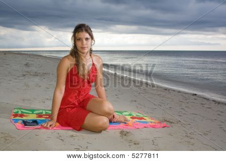 Attractive Girl With Red Dress Sitting Beside A Book