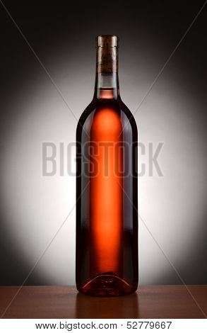 A blush wine bottle backlit with a light to dark spot background. Vertical format.