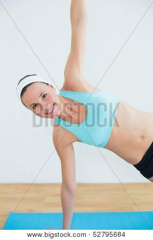 Portrait of a slim young woman doing the side plank yoga pose in fitness studio
