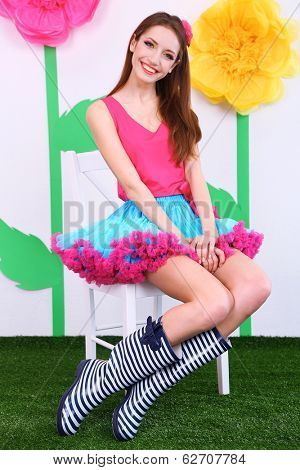 Beautiful young woman in petty skirt sitting on chair on decorative background
