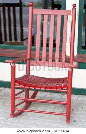 Red Wooden Rocking Chair In Front Of Store Window